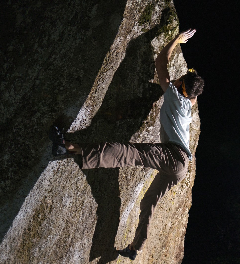 young man climbing a sheer rock face, reaching up with one hand